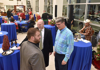 (Brad Davis/The Register-Herald) Mountaineer Automotive co-owner Donnie Holcomb, right, chats with United Bank employees Chaz Turner, left, and WIlliam Turner as Meadow Bridge musician Gabe Dixon sings for those in attendance at the Eisenhower Drive dealership's silent auction and Christmas fundraising party for Mac's Toy Fund Thursday night.