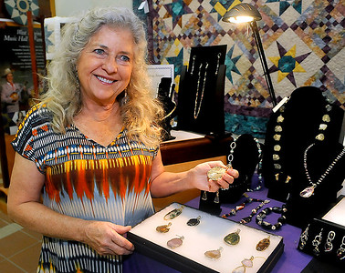 Brad Davis/The Register-Herald Lewisburg area jeweler and gem cutter Marty Schaerer shows some of her work to interested patrons during an Appalachian Festival artist demonstration event Sunday afternoon at Tamarack.