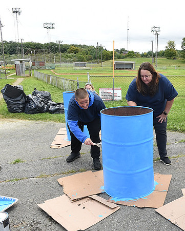 ResCare employees, Megan Guire, home manager, left, Cathy Redden, executive director and James Goode, resident, painting trash barrels at Beckley Little League fields off Eisenhower Drive. ResCare is a behavior Health Agency that provides residential services for people with intellectual disabilities. The agency picked Beckley Little league for their give back to the community project by providing a combined thirty employees and residents to spruce up five fields.<br /> (Rick Barbero/The Register-Herald)