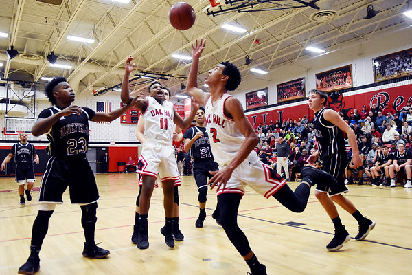 Oak Hill's Michael Beasley (2) and Jason Manns (11) go for an offensive rebound as Bluefield's Jamere Edwards (23) and Braden Crews (30) look on during the second quarter of their basketball game Tuesday in Oak Hill. (Chris Jackson/The Register-Herald)