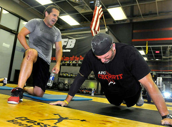 Chip Williams, left, pushes fellow athlete Tommy McClung as he keeps count of his pushups during a CrossFit session July 15 at L.A. East Fitness on Mountaineer Drive. Brad Davis/The Register-Herald