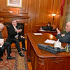 (Brad Davis/The Register-Herald) Rocket Boy Homer Hickam, left, signs a couple of his books for governor Jim Justice at the conclusion of a meeting between him, Theatre West Virginia's Scott Hill, right of Hickam, and Allen Media Strategies' Burke Allen (unphotographed) Monday afternoon in Charleston.
