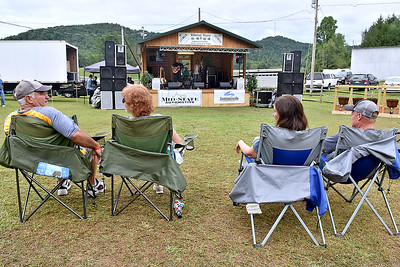 (Brad Davis/The Register-Herald) Patrons relax as they take in a show from The Bandwagon Band out of Hamlin at the Kirkwood Wine Festival Sunday afternoon in Summersville.