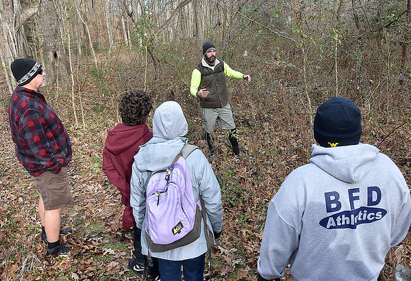 """(Brad Davis/The Register-Herald) Doubling as part trail and tour guide, Active Southern West Virginia Senior Community Captain Levi Moore, upper middle, shows a group of hikers the site of former mine company baseball field as they embark on a light, 2.5 mile journey along the Timber Ridge, Fayetteville and Long Point trail loop as they """"Opt Outside"""" instead of partaking in the long lines and hustle of Black Friday shopping Friday afternoon at the Long Point trailhead. Active Southern West Virginia community captains Levi Moore and Hilarie Jones, among others, helped organize the annual hike, which began with the basic idea of encouraging outdoor recreation instead of consumer shopping."""