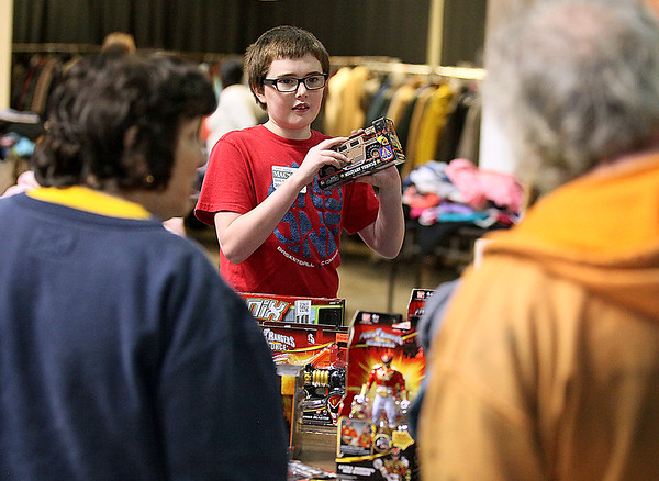 Brad Davis/The Register-Herald 11-year-old volunteer Noah Turner, quite possibly an excellent future salesman, shows off and describes various toys to prospective shoppers during Mac's Toy Fund Party Saturday morning at the Beckley-Raleigh County Convention Center.