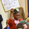 (Brad Davis/The Register-Herald) Gwen Lacy, a teacher at Fall River Elementary School (McDowell County) with 40 years of service, holds a sign during a PEIA public hearing Wednesday night at Tamarack.