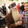 Jerry Malone, Vietnam veteran, left, recieves a American flag from, Sedrice Foster, pre-k, during a Veteran's Day program held at Lester Elementary School Wednesday afternoon. All veterans that attended the program received flags from the pre-k students.<br /> (Rick Barbero/The Register-Herald
