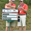 (Brad Davis/The Register-Herald) A pair of sign-carrying volunteers talk golf as they monitor the standings while their group putts on 12 during the second round of the Military Tribute at The Greenbrier Thursday afternoon in White Sulphur Springs.