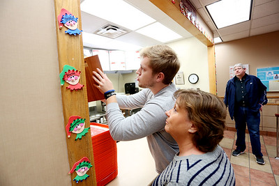 Jarod Cline hangs a plaque on the wall at Wendy's where his mother, Sherry Acord-Cline, worked for 33 years before passing away last month, as her twin sister Sherl Grow, center, and Sherry's husband Darrell Cline look on at the restaurant in Beaver on Monday. (Chris Jackson/The Register-Herald)