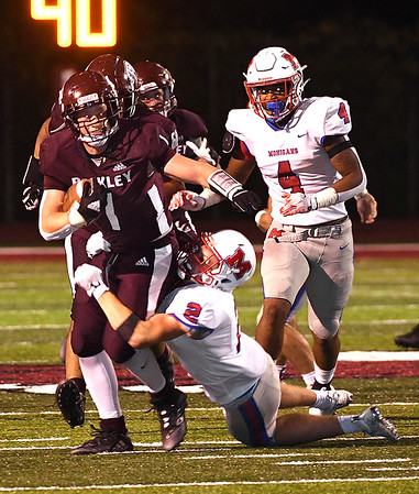 Maddox McMillen, of Woodrow Wilson, left, drags, Jarrett Lawrence, of Morgantown, for some extra yards in the first half during game held at Woodrow Wilson High School.<br /> (Rick Barbero/The Register-Herald)
