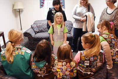 Alea Harper, 8, gets her science apron adjusted by Jessica martin, the troop leader for Brownie Troop 37400 from White Sulphur Springs, during the WVSOM Science Fair Carnival in Lewisburg Saturday.  (Chris Jackson/The Register-Herald)
