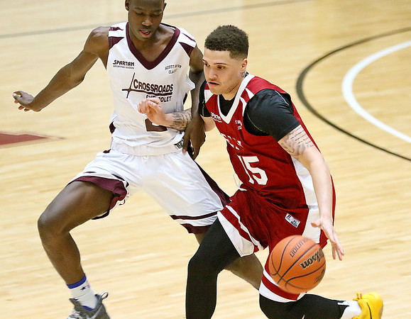 (Brad Davis/The Register-Herald) WVU recruit Teddy Allen moves the ball up the court as Crossroads' (Class AAA) Darius George defends during the Scott Brown memorial game Saturday evening at the Beckley-Raleigh County Convention Center.