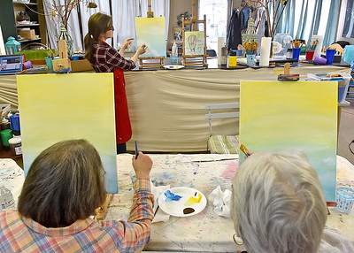 """(Brad Davis/The Register-Herald) Mt. Hope residents Ramona Brown, right, and Dolly Lilly spend a Sunday painting what will eventually be a scene of hot air balloons in an afternoon sky using acrylics on canvas as instructor Lynsi Boyd helps them with tips and tricks during a studio painting session at 110 Marshall in Beckley. The art studio and music venue usually has similar paiting parties scattered throughout the year including on some Sundays. Painting sessions are often themed in a variety of ways designed to help painters build skills in painting certain types of objects or textures, with yesterday's being """"Up, Up an Away"""" in reference to the balloons. Similar upcoming painting events will be """"Peaceful River"""" on Monday, March 27 at 6:00 p.m. and """"Angel Wings"""" Friday, April 7 at 6 p.m. Keep an eye on their facebook page or give them a call at 304-634-8367."""