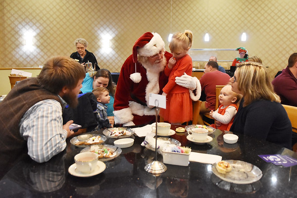 """Santa Claus speaks with Claira Nelson, 3, as her father John Nelson, left, and mother Hannah Nelson, with 9-month-old Haley, during """"Tea with Santa"""" as part of the Santa Christmas Adventure at The Resort at Glade Springs on Saturday. (Chris Jackson/The Register-Herald)"""