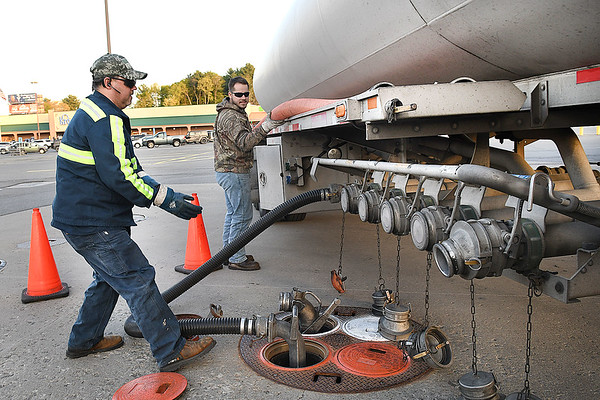 Eddie Owens, left and Christian Trent, of PTC from Roanoke, Va. pumps in 3500 gallons of unleaded gas into Krogers at Beckley Crossing empty 20,000 gallon tank. Krogers on Harper Road was also empty and they provided them with 5000 gallons.<br /> (Rick Barbero/The Register-Herald)