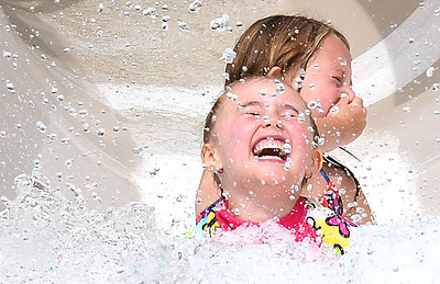 """Rilee Workman, 5, of Beckley, front, and Ava Lively, of Beckley, 6, slide down the waterslide together at the New River Park pool in Beckley Monday morning during their summer day camp held by St. Francis de Sales School. The camp is called """"Camp Down Under"""" and takes place Monday to Friday from 7:30 am to 5:30 p.m. The camp offers a variety of outdoors events, arts and crafts and will be studying about Australia. Thursday, July 25 they will put on a progam in costumes with dancing and music. The Camp ends August 2. (Rick Barbero/The Register-Herald)"""