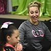 Miranda Elkins, assistant cheer coach for GymFinity All-Stars, works with the girls at the gym in Oak Hill.