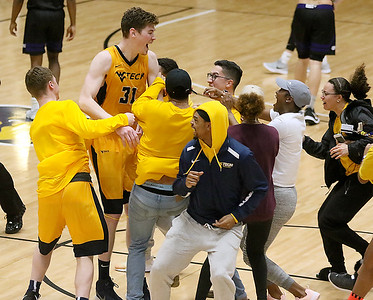 (Brad Davis/The Register-Herald) WVU Tech senior Michael Scott is mobbed by celebrating students after they rushed the court following a comeback victory over Asbury Wednesday night at the Beckley-Raleigh County Convention Center.
