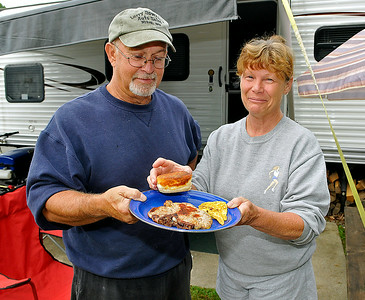 Phillip and Becky Weaver show off the finished product, a hearty breakfast fit for a camper, early Sunday morning at the Lake Stephens RV campground. The former Lincolnton, North Carolina residents spend virtually every weekend camping at Lake Stephens, and they've quickly developed a tradition of making one of the best homemade, open fire-cooked breakfasts around. They now live in the Morgan Hills area, and word of the Weavers' awesome biscuits is beginning to spread outside the campground thanks to camping neighbors lucky enough to get a shot at whatever's left over. Brad Davis/The Register-Herald