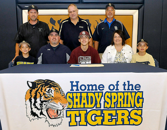 Shady Spring standout athlete Jordan Meadows signed a letter of intent to play baseball at Concord University surrounded by coaches and family Monday afternoon in the Tigers' gymnasium. Joining him at the table are his little brothers Jason (far right) and Jacob (far left), his parents Sheila and Scotty (left of Jordan), Shady Spring Athletic Director Steve Clark (back row middle) and baseball coaches Darrell Frasier (back row left) and James Sears (back row right). Brad Davis/The Register-Herald