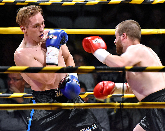 (Brad Davis/The Register-Herald) Beckley's native Tyler Robinson, left, battles Tyler White in the night's first professional bout during Original Toughman action Saturday night at the Beckley-Raleigh County Convention Center.