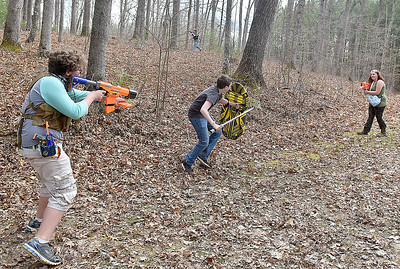 (Brad Davis/The Register-Herald) Combatants contest a key path along the battle field during Nerf War at Lake Stephens Saturday afternoon. The free event, another in a line of fun, physical activities presented by Active Southern West Virginia, pits two teams of warriors against each other in capture the flag-style games, using the famous foam armaments of all types, from guns and pistols to axes, swords and shields, all provided by ASWV. Keep an eye on their Facebook page and website for upcoming events including more Nerf Wars, which have been a huge hit so far.