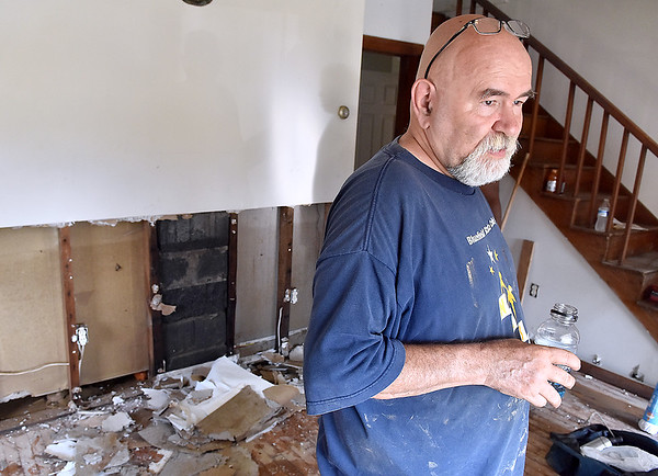 (Brad Davis/The Register-Herald) Washington Street resident Roy Grimes looks over his flooded home Sunday afternoon in Alderson. His daughter Brin and son-in-law Daryl came to spend the day helping him with the cleanup process.