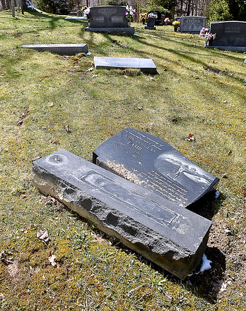 (Brad Davis/The Register-Herald) The broken and displaced monuments marking the graves of Ghent resident Patti Morum's late son John Lamb, near, and her parents Lacy and Beth Meador rest the way they were recently discovered inside the Meador family cemetery Sunday afternoon.