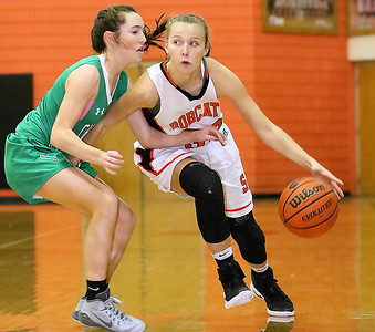 (Brad Davis/The Register-Herald) Summers County's Whittney Justice looks for an open teammate as she holds off Charleston Catholic's Mills Mullen while rushing up the court during the Lady Bobcats' win over the Irish Saturday night in Hinton.