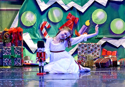(Brad Davis/The Register-Herald) Clara, played by Louie Boyd, begins to get sleepy as she plays with her Christmas gift during a scene from Beckley Dance Theatre and Beckley Performing Arts' presentation of The Nutcracker Sunday afternoon inside the Woodrow Wilson High School Auditorium.