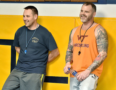 (Brad Davis/The Register-Herald) Greenbrier West wrestling coaches Steve and Jeremy Tincher have a few laughs as they watch their wrestlers warm up prior to a practice Friday afternoon in Charmco.