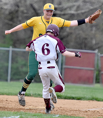 (Brad Davis/The Register-Herald) Greenbrier East 1st baseman David Hofmann has to leap to take a high throw down the first base line as Woodrow Wilson's Johnie Clay would beat his tag on the way down to end up safe on a bunt Wednesday evening in Beckley.