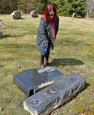 (Brad Davis/The Register-Herald) Ghent resident Patti Morum looks over the broken and displaced monument marking the grave of her late son John Douglas Lamb inside the Meador family cemetery Sunday afternoon.