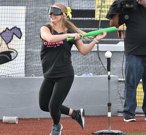 """(Brad Davis/The Register-Herald) Beckley resident Chelsey Peters, dizzy after a few spins prior and disoriented from the """"drunk"""" goggles, spins completely around after a big swing and miss, one of a few, as she plays the """"don't drink and drive"""" game between innings Wednesday night at Linda K. Epling Stadium."""