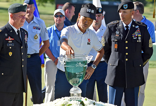 (Brad Davis/The Register-Herald) Servicemembers on hand look on as event champion Kevin Na can't resist getting a quick touch of his shiney new trophy prior to the ceremony after winning the Military Tribute at The Greenbrier Sunday afternoon in White Sulphur Springs.