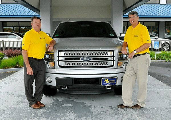 Brad Davis/The Register-Herald   Mountaineer Automotive owners Donnie Holcomb, right, and Keith Tyler pose for a quick photo outside of their dealership at the old Ramey Ford location on Eisenhower Drive July 28.