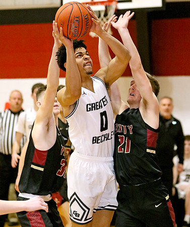 (Brad Davis/The Register-Herald) Greater Beckley Christian's Jay Moore powers his way to the basket for a layup through Trinity's Fletcher Hatsock, left, and Briston Bennett Saturday afternoon in Prosperity.