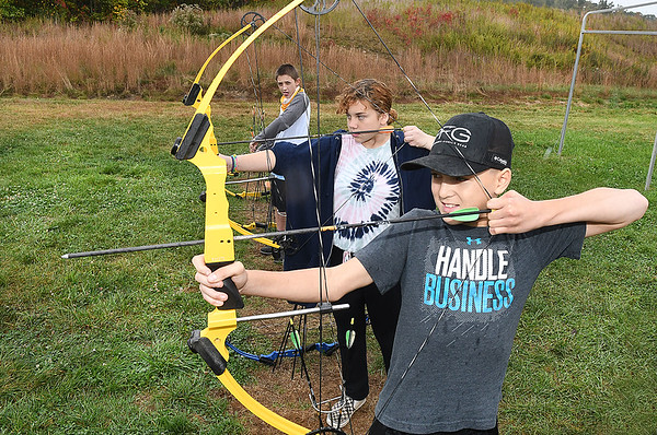 Midland Trail Middle school Students, Austin Sears, far left, Kaylynn Knight and Kolton Eades, practice shooting an bow and arrow after leaning the  Samuel Shumate, left, and Jaxon Barnhouse, learning the science on how different types work with weight difference, design features and how each bow feels during WVU Adventure School held at the Summit Bechtel Reserve in Glen Jean.<br /> (Rick Barbero/The Register-Herald)