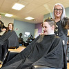 (Brad Davis/The Register-Herald) Stylist Stacey Conkle (far right), owner of Get Faded & Dye Salon, shares a laugh with customer and Pinehaven resident Luka Bruffy as she holds up a huge chunk of hair taken off as part of her undercut style do, while fellow resident Brittany Farrell gets a haircut from stylist Tyjhea Grandjean Wednesday afternoon. Get Faded & Dye spent the day providing free haircuts to residents of Pinehaven Homeless Shelter while free transportation to and from was provided.