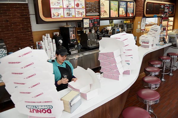 Preshma Dhakal preparing boxes for donuts at the Donut Connection.<br /> (Rick Barbero/The Register-Herald