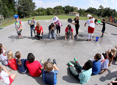 Brad Davis/The Register-Herald Mabscott Elementary students from the 3rd, 4th and 5th grades gather at the playground Friday afternoon to watch their teachers get doused with ice cold water as they answer Cranberry Elementary's nomination take part in the ALS Ice Bucket Challenge. From left is Mabscott teacher Emily Greene being doused by student Taejhonna Williams-Dancy, Adriana Boone being doused by student James O'Hara, Kellie Snuffer being doused by student Carlella Branch, Christy Delp being doused by student Amber Bowman and Crystal Lockhart being doused by students Kayla Bayne and Landon Davis.