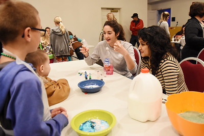 WVSOM Medical Students Maryian Gheissari, center, and Pavitri Dwivedi, right, show Jayden Ferrara, 9, and Sebastian McVaugh, 5, both from Lewisburg, a science demonstration during the WVSOM Science Fair Carnival in Lewisburg Saturday. (Chris Jackson/The Register-Herald)