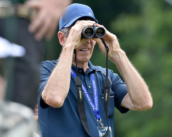 (Brad Davis/The Register-Herald) A fan utilizes binoculars as he scans the distant fairway for incoming pro golfers during the second round of the Military Tribute at The Greenbrier Thursday afternoon in White Sulphur Springs.