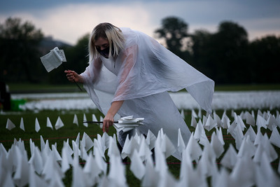 A volunteer places flags on the National Mall for COVID-19 memorial