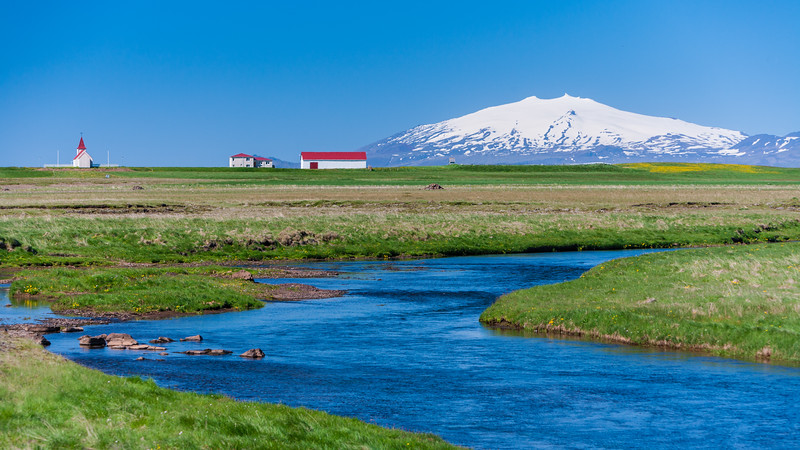 View of Icelandic farm, with Snaefellsjokull volcano in the distance.