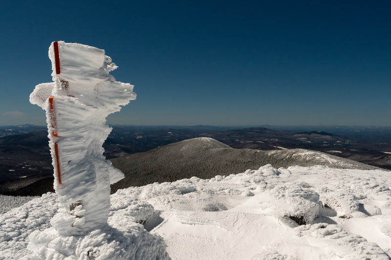 The Moosilauke summit signs carry long rime-ice feathers.