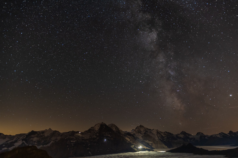 Stars and the Milky Way over the Berneralps, seen from the summit of Faulhorn. Eiger's Mittelegihütte (left), mid-face Station Eigerroand, and Station Eigergletscher, are bright points on its face.
