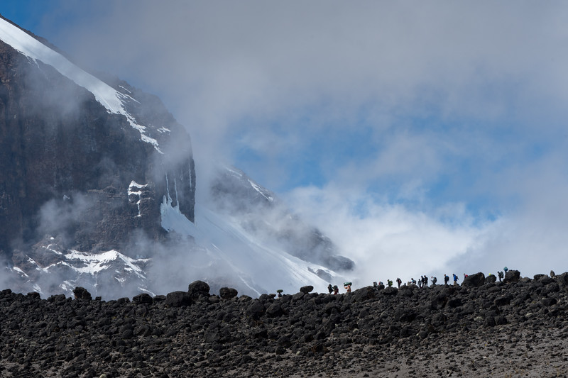 Porters and trekkers are visible along the near ridgeline, with the summit ridge of Kilimanjaro behind.