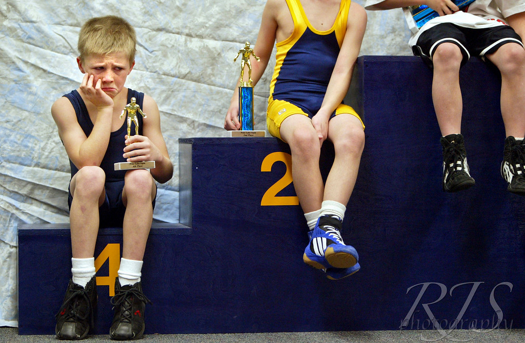 Jimmy Cates, 8, of Prior Lake is not too happy about posing with his trophy after competing in a youth wrestling tournament at Prior Lake High School on Saturday, January 3, 2004. But having just competed in his first wrestling tournament ever and after only three practices, Jimmy did remarkably well, said his mother Terri Cates. Jimmy placed fourth out of four boys in his age group and ability.