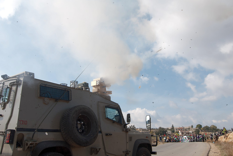 An Israeli army vehicle fires teargas canisters into the crowd 以色列軍車向群眾發射催淚彈